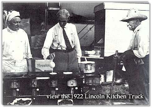 Henry Ford tries his hand at cooking flapjacks. At the rear are two of the special trucks which accompanied the campers.