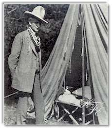 Henry Ford in cowboy hat and neckerchief, poses outside his tent.