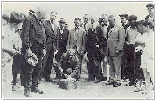 This photo was taken on August 5, 1919 during the vagabonds' camping trip, and shows Henry Ford carving his initials on the stone which became the cornerstone of his manufacturing plant at Green Island, New York, which to this day is the key plant of Ford's Engine and Foundry Division. Others in the picture include Thomas A. Edison, holding cap; Harvey Firestone, standing behind Mr. Ford; John Burroughs, the bearded naturalist and writer, on Mr. Firestone's left; Cornelius Burns, then mayor of Troy, N.Y ., in which the plant is located, on Mr. Firestone's left; and James R. Watt, then mayor of Albany, standing between Messrs. Edison and Ford. Photo from Ford's Green Island Plant.